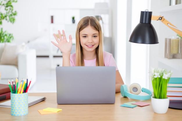 Фотография позитивной девочки, изучающей ноутбук с дистанционным использованием, общение в онлайн-классе, общение с учителем, приветствие, волна, рука, стол, письменный стол в доме, в помещении