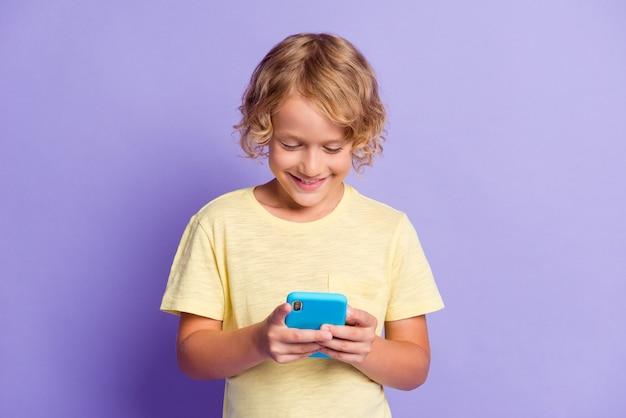 Фотография позитивного маленького мальчика, болтающего по мобильному телефону, в желтой футболке, изолированной на фиолетовом фоне
