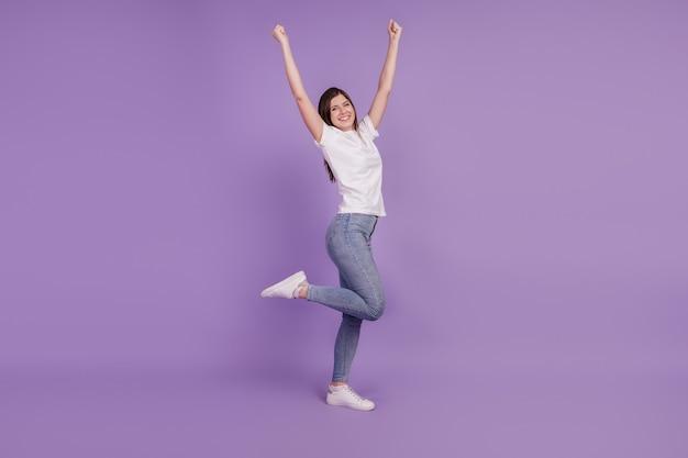 보라색 배경 위에 격리된 긍정적인 행운의 소녀가 주먹을 들고 승리하는 사진