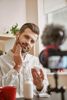 ライブストリーミング中に顔に化粧用クリームを塗っているポジティブな男性美容ブロガーの写真。