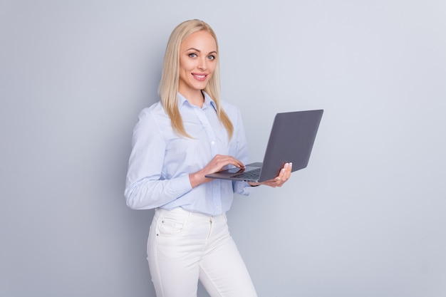 긍정적 인 관리자 여자의 사진은 회색 벽에 노트북 미소를 개최