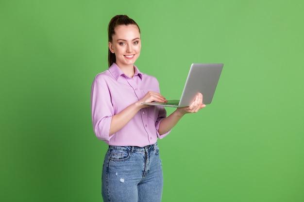 긍정적인 매니저 소녀가 원격 노트북 문자를 입력하는 사진은 소셜 네트워킹 통신 wi-fi 연결을 즐깁니다. 녹색 배경 위에 격리된 라일락 데님 청바지를 입고