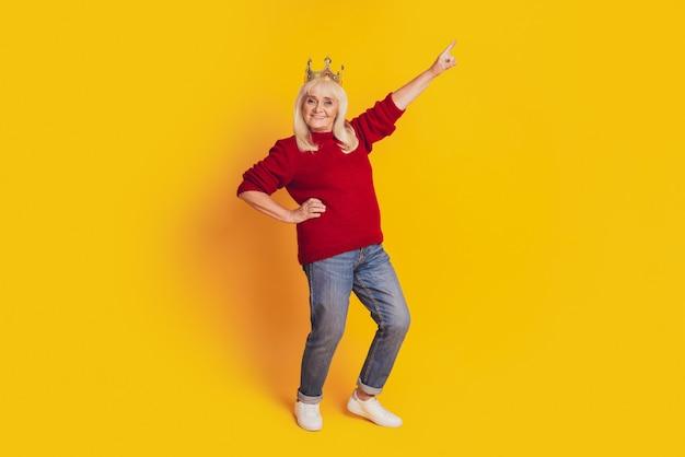 Фотография позитивной старухи с золотой короной указывает пальцем пустое пространство