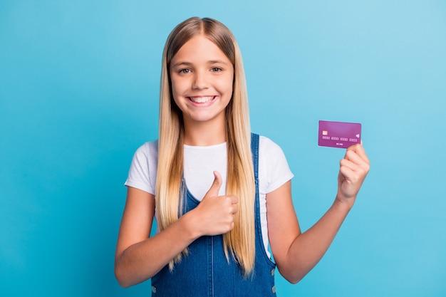 Фотография позитивной девушки-подростка с красивыми светлыми волосами, держащая банковскую карту, показывает знак ок, носит повседневную одежду, изолированную на пастельно-синем цветном фоне
