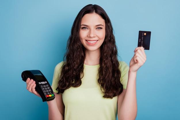 肯定的な信頼できる女性の写真は、青い背景にデビットカードポータブルワイヤレス端末を示しています