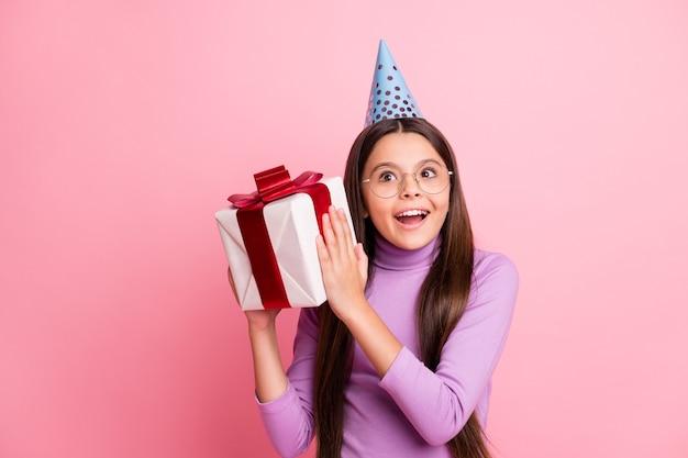 Фотография позитивно потрясенной маленькой девочки встряхивает подарочную коробку в фиолетовой шапочке на день рождения, изолированной на пастельном цветном фоне
