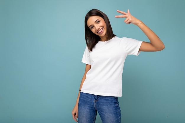 복사 공간 파란색 배경 위에 절연 모형에 대 한 캐주얼 흰색 티셔츠를 입고 성실한 감정과 긍정적 인 미소 즐거운 젊은 아름 다운 갈색 머리 여자의 사진.