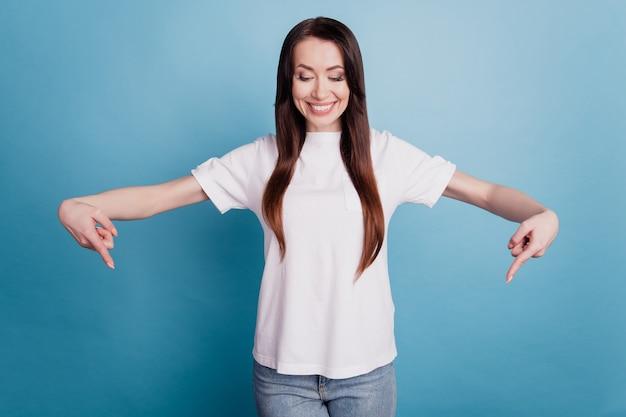 파란색 배경 위에 격리된 긍정적인 여성 포인트 손가락의 사진