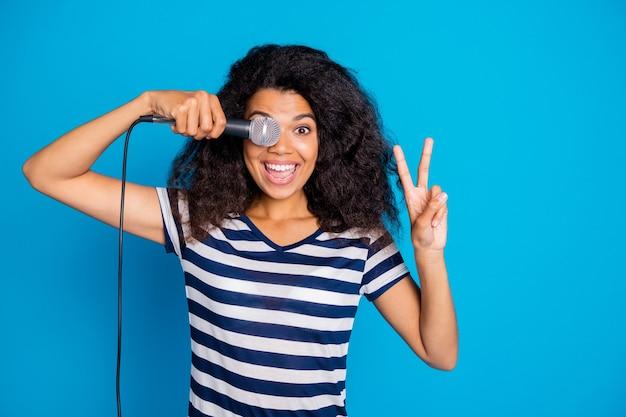 마이크로 눈을 덮고있는 v 기호를 보여주는 긍정적 인 여성의 사진