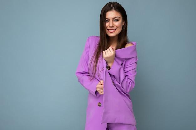 青い背景に分離された紫色のスーツを着ているポジティブな若いビジネスの長い髪のブルネットの女性の写真。コピースペース