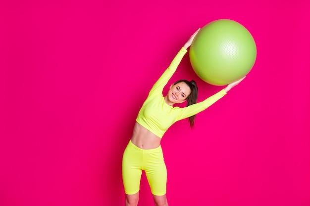 ポジティブな若いスポーツウーマンの写真は、ピンクの輝きの色の背景の上に分離された背中を伸ばしてフィットボールを曲げます
