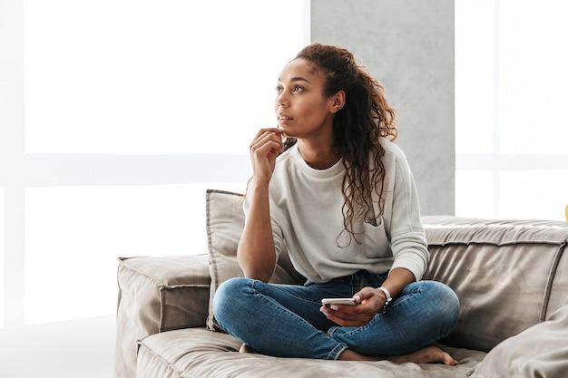 明るいアパートのソファに座って、携帯電話を使用してかなりアフリカ系アメリカ人の女性の写真