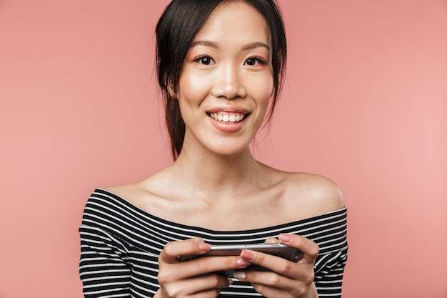 기본 복장을 한 예쁜 아시아 여성이 빨간 벽에 격리된 스마트폰을 들고 웃고 있는 사진