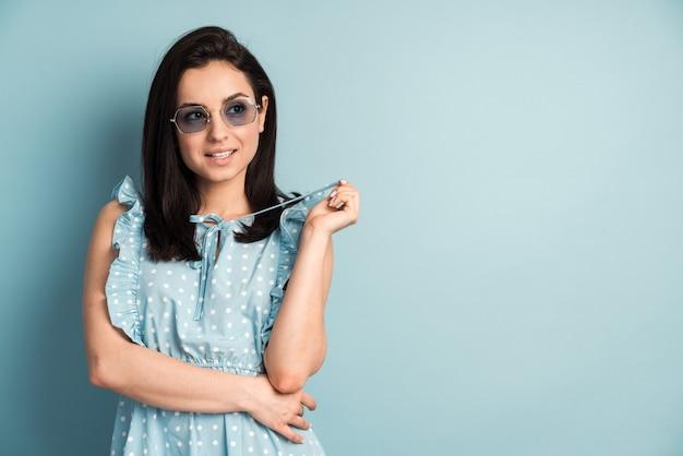 파란색 벽에 고립 된 스트라이프 캐주얼 여름 봄 드레스를 입고 꽤 매력적인 아가씨의 사진