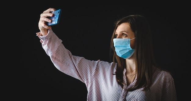 かなり魅力的な女性の写真は、社会的な距離を保ち、電話をかけて自分撮りをオンラインブログにします