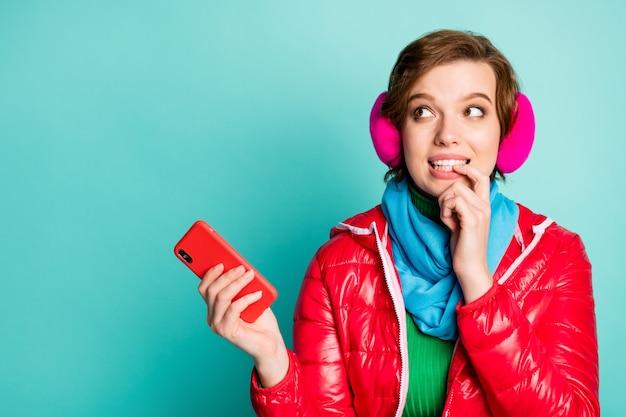 かなり美しいおかしい女性の写真は、興味を持って空のスペースを噛んで電話を保持します赤いコートスカーフピンクの耳は緑のジャンパー孤立したティール色の壁をカバー