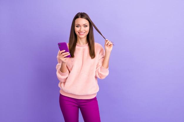 보라색 벽에 긴 컬을 가지고 노는 전화를 들고 예쁜 블로거 아가씨의 사진