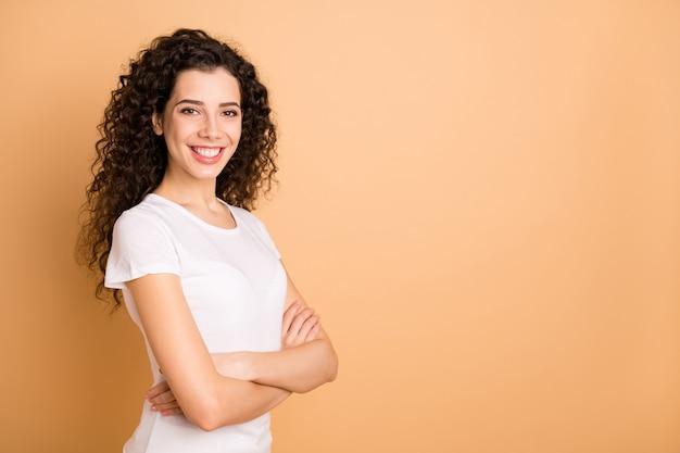 교차 팔 이빨 빛나는 미소와 예쁜 비즈니스 아가씨의 사진은 흰색 캐주얼 옷을 입고 베이지 색 파스텔 색상 배경에 고립