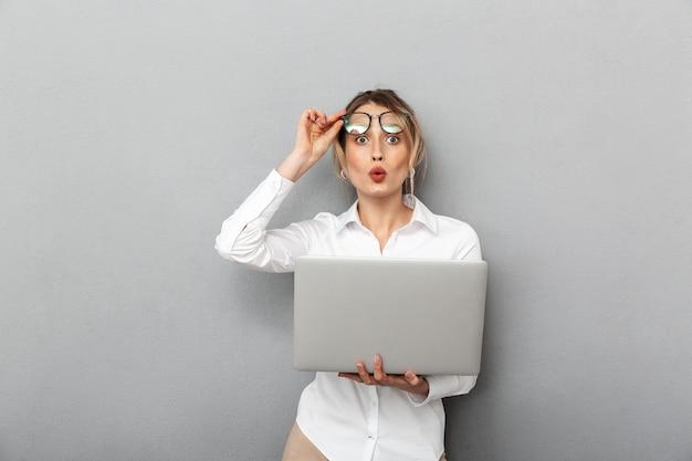 眼鏡をかけて立って、オフィスでラップトップを保持しているかなりビジネスライクな女性の写真、孤立