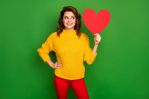 かなり魅力的な波状の女性の写真は紙のハート型のポストカードロマンスの日付の招待状を保持します答えを考えてください黄色のニットセーター赤いズボンは明るい緑色の壁を分離しました