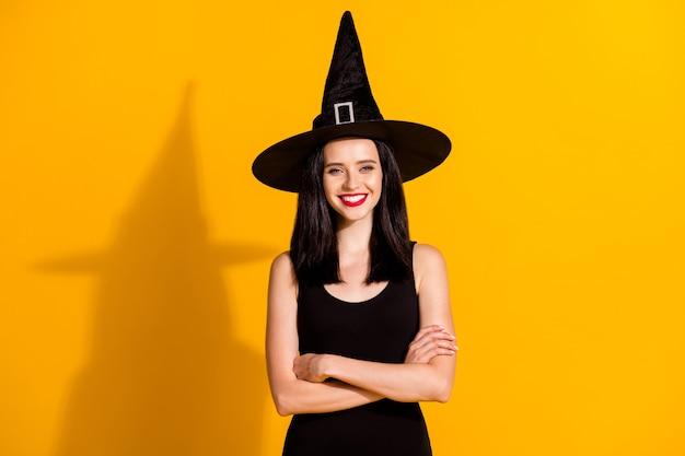 かなり魅力的な若い魔術師の女性の写真光沢のある笑顔の折りたたまれた手自信を持ってルックホールドテーマイベントホームウェア黒の帽子ドレス孤立した明るい黄色の背景