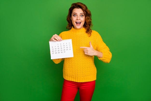 Фотография довольно жизнерадостной женщины с прямым бумажным календарем с пальцами, показывающая месяц без планов, удивительный планировщик, одетый в желтый вязаный свитер, красные брюки, изолированные на стене зеленого цвета