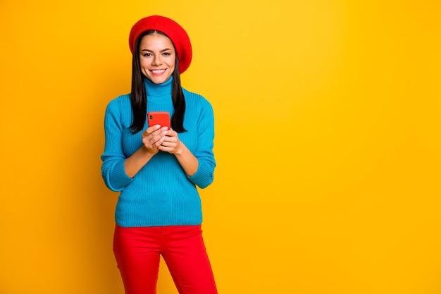 Фотография довольно жизнерадостной латинской леди держит телефонный разговор с друзьями в берете, синий свитер с высоким воротом, красные брюки, изолированные ярко-желтого цвета на стене