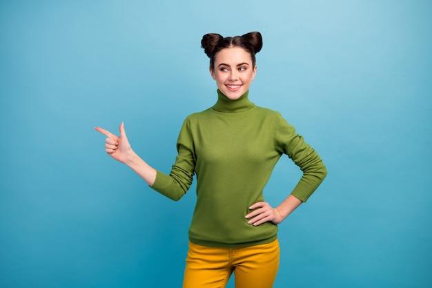 Фотография довольно любопытной женщины, менеджер по продажам, работник, прямой палец, пустое пространство, предлагает низкие цены, одежда для покупок, зеленая водолазка, желтые брюки, изолированные на стене синего цвета