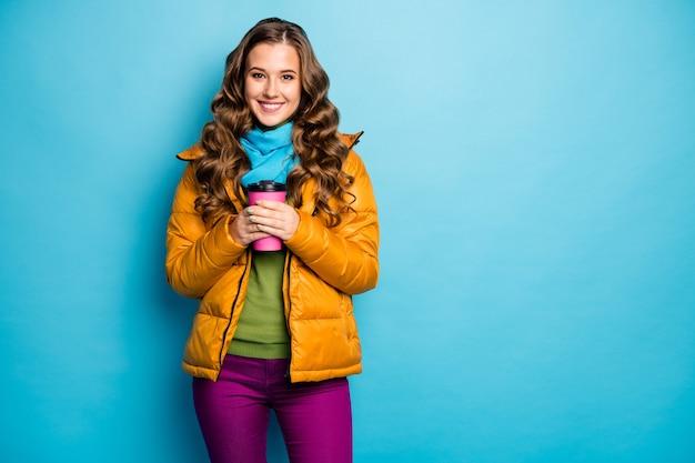 かなり巻き毛の女性の写真は、熱い紙の飲料マグを保持します暖かい天候をお楽しみくださいカジュアルな黄色のオーバーコートスカーフバイオレットのズボン緑のジャンパー孤立した青い色の壁