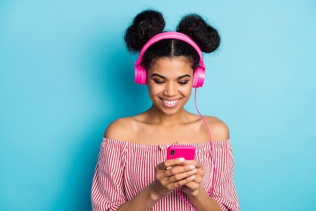 꽤 어두운 피부 아가씨의 사진 전화 채팅 친구 듣기 음악 현대 기술 이어폰 착용 빨간색 흰색 줄무늬 셔츠 벗은 어깨 절연 파란색 벽의 사진
