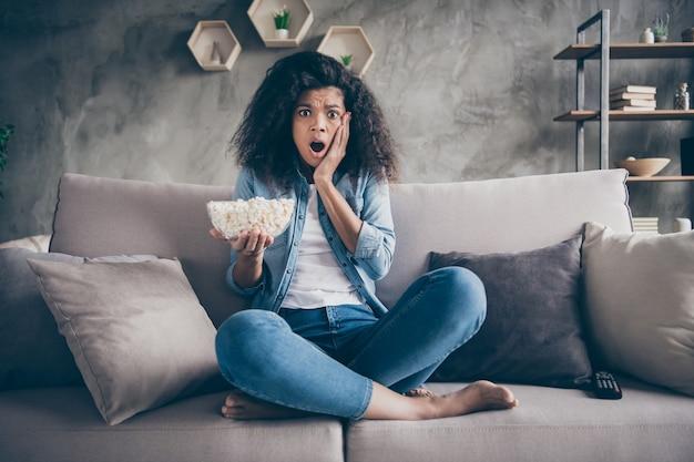 Фото симпатичной темнокожей волнистой дамы в домашнем настроении, поедающей попкорн, смотря телешоу ужасов, положив руку на щеку, сидя на уютном диване, повседневная джинсовая одежда, квартира в помещении