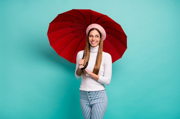 Фотография симпатичной мечтательницы-путешественницы с большим красным зонтиком на прогулке по улице за границей, хорошее настроение, одежда, характеристики, розовый берет, белая водолазка, полосатые джинсы, изолированный, бирюзовый цвет фона