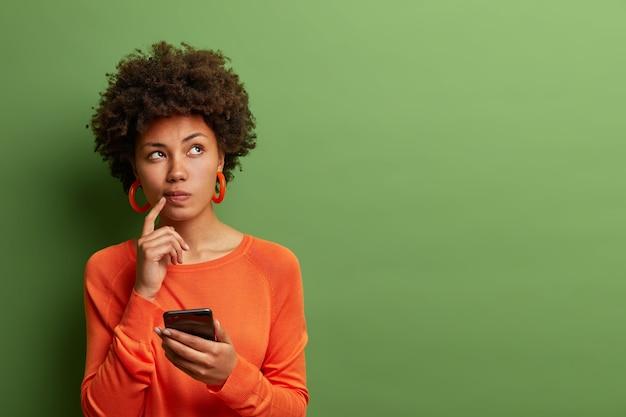 예쁜 민족 여성의 사진은 질문에 답하는 방법을 숙고하고, 무언가에 대해 깊이 생각하고, 현대적인 휴대 전화를 사용하고, 좋은 메시지를 작성하려고, 검지 손가락을 입술 가까이에 두며, 실내에 서 있습니다.