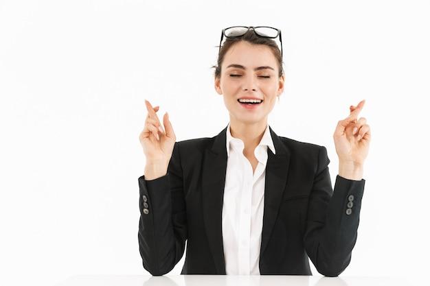 白い壁に隔離されたオフィスの机に座って仕事をしている間、指を交差させて正装を着たきれいな女性労働者の実業家の写真