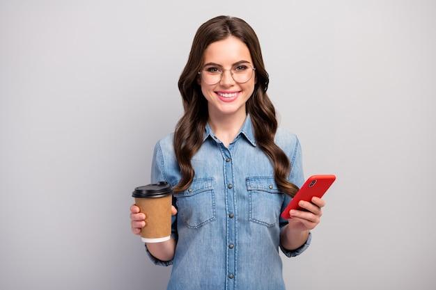 Фотография симпатичной женщины-фрилансера, держащей бумажный стаканчик, горячий кофе, напиток, перерыв, просмотр телефонного устройства, характеристики одежды, повседневные джинсы, джинсовая рубашка, изолированный серый цвет