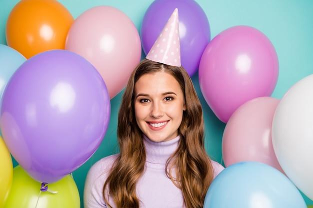 많은 다채로운 공기 풍선으로 둘러싸인 꽤 재미있는 생일 아가씨의 사진 최고의 휴가는 청록색에 종이 이벤트 모자 라일락 풀오버를 착용합니다.