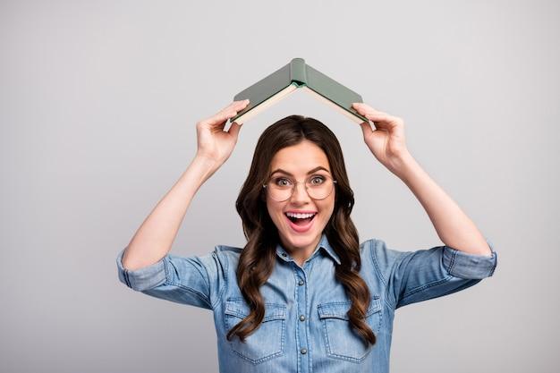 Фотография довольно забавной сумасшедшей дамы с книгой над головой хорошее настроение не хочу учиться хочу радоваться технические характеристики повседневные джинсы джинсовая рубашка изолирована серого цвета