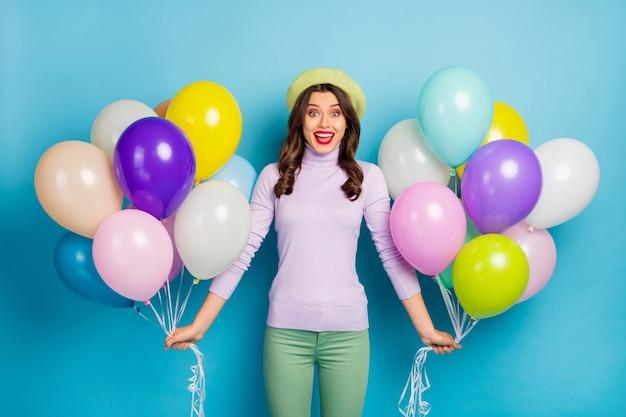 かなり面白い女性の写真は、多くのカラフルな気球を運びます予期しないサプライズパーティーウェア紫のセーターベレー帽キャップ緑のズボン孤立した青い色の壁