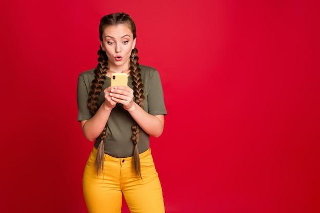 新しい肯定的なコメントを読んで電話を保持しているかなり面白い女性の長い三つ編みの写真口を開けてカジュアルな黄色のズボンを着用緑のtシャツ孤立した赤い色の背景
