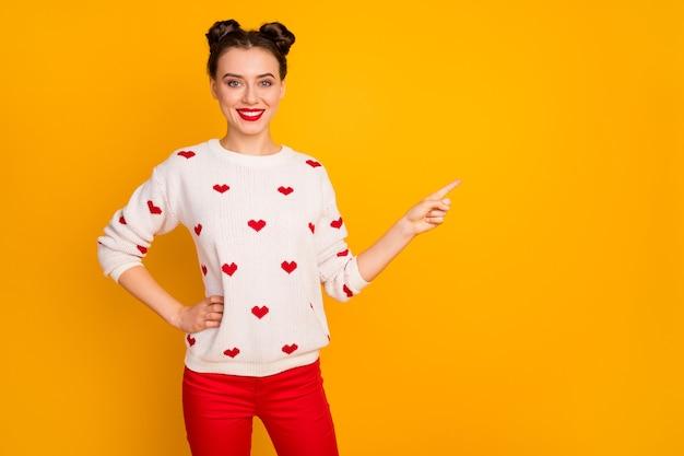 Фотография довольно забавной дамы, показывающей низкие цены распродажи, указывая пальцем на пустое пространство, баннерная реклама, белый пуловер с узором сердечек