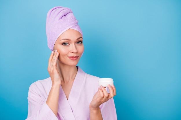 예쁜 여자가 크림 항아리를 들고 있는 사진은 강장제 모양의 카메라를 입고 보라색 수건 터번 목욕 가운을 입고 파란색 배경을 분리했습니다.