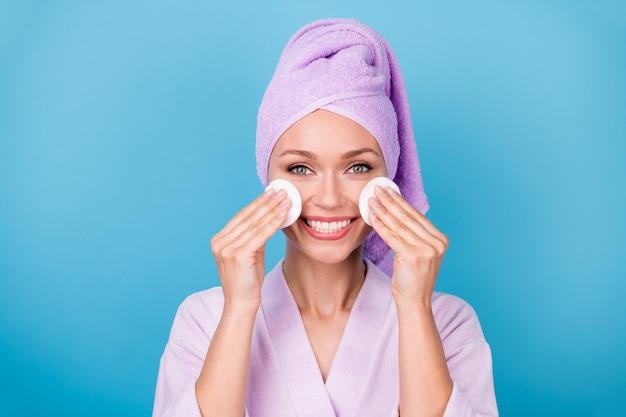 예쁜 여자가 두 손을 들고 있는 사진은 면 디스크 얼굴을 입고 보라색 수건 터번 목욕 가운을 입고 파란색 배경을 분리했습니다.