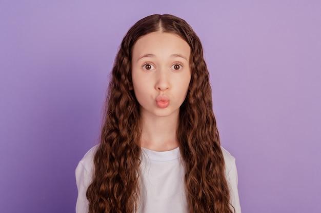 紫色の背景の上に分離された空気のキスを送信するかわいい女の子の写真