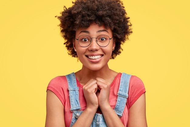 気持ちの良い笑顔で、かなり幸せな暗い肌の女性の写真は、手をつないで、良い賞賛の言葉を受け取り、巻き毛を持ち、黄色い壁にポーズをとっています。嬉しいアフリカ系アメリカ人の女性