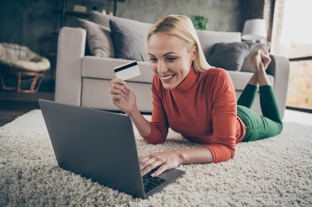 インターネットのウェブサイトを選択するかなり家庭的な女性の写真ノートブック購入は、ソファの近くのカーペットの床に横たわっている支払いのために準備されたクレジットカードカジュアルな服装のリビングルーム屋内