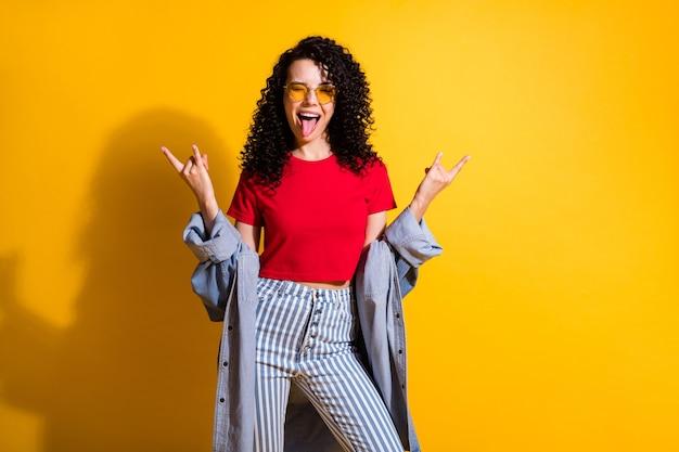 예쁜 아가씨가 눈을 깜박거리며 혀를 내밀고 있는 시시덕거리는 쇼 뿔이 빨간색 티셔츠 줄무늬 청바지 재킷을 입고 노란색 배경에 격리된 사진
