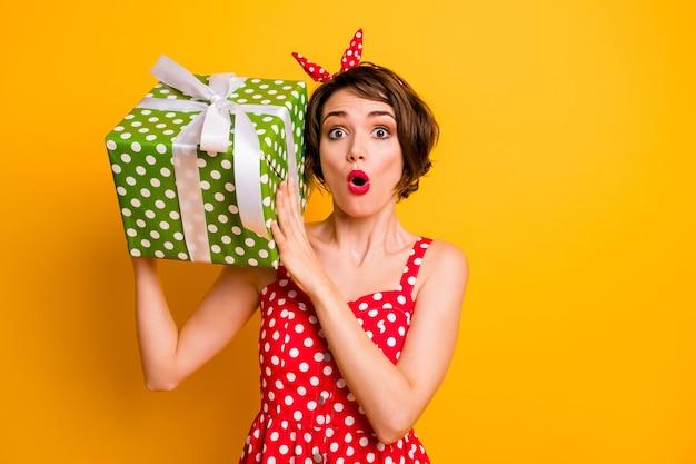 Фотография симпатичной дамы держит большую зеленую подарочную коробку возле уха с открытым ртом взволнованная именинница носит ретро-стиль пунктирное красное белое платье, оголовье изолированной стены желтого цвета