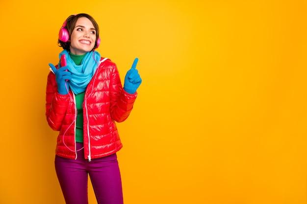 예쁜 아가씨의 사진 스마트 폰 들어 이어폰 댄스 파티 쿨링 무드 착용 캐주얼 레드 코트 블루 스카프 장갑 바지