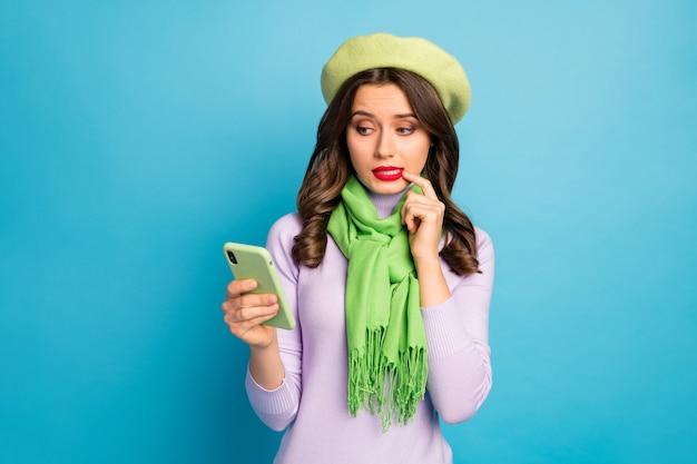 きれいな女性の写真は、指を噛む電話の手を握る新しい投稿テキストは緑色のベレー帽の帽子を着用する紫色のタートルネックのスカーフは明るい青色の壁を分離しました
