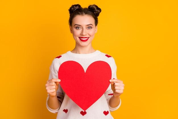 Фотография симпатичной дамы с большим бумажным сердцем, демонстрирующей творческую идею, открытка на дату, приглашение, носить белый красный свитер с узором сердца
